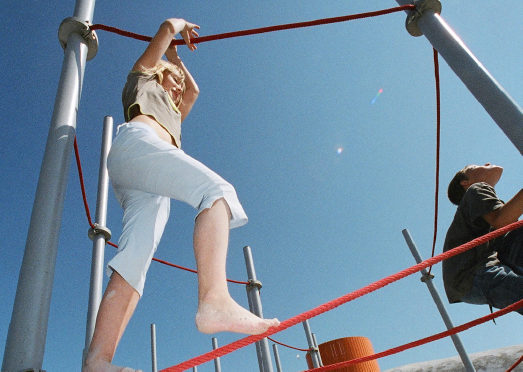 Mädchen klettert auf einem Seil.